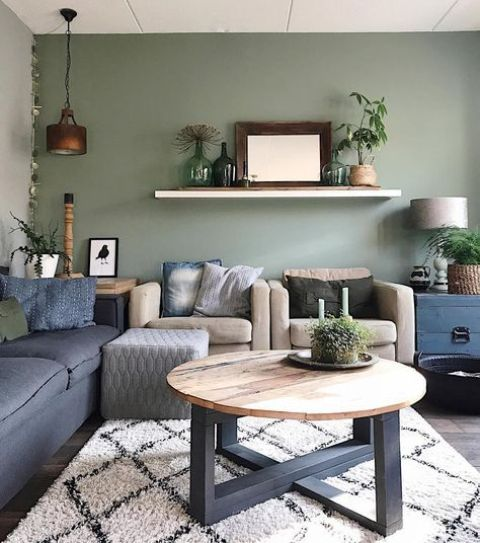 a modern boho living room with a sage green accent wall, a navy sofa and tan chairs, a round table and potted plants around