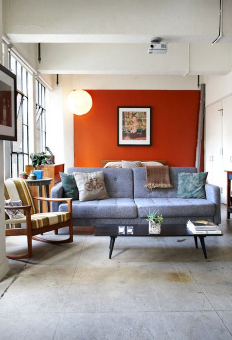 a modern living room with an orange accent wall, a grey sofa, a striped chair, a low coffee table and some bold artworks