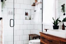 a modern white bathroom with various types of tiles, a dark stained floating vanity and a matching mat and bench, potted greenery