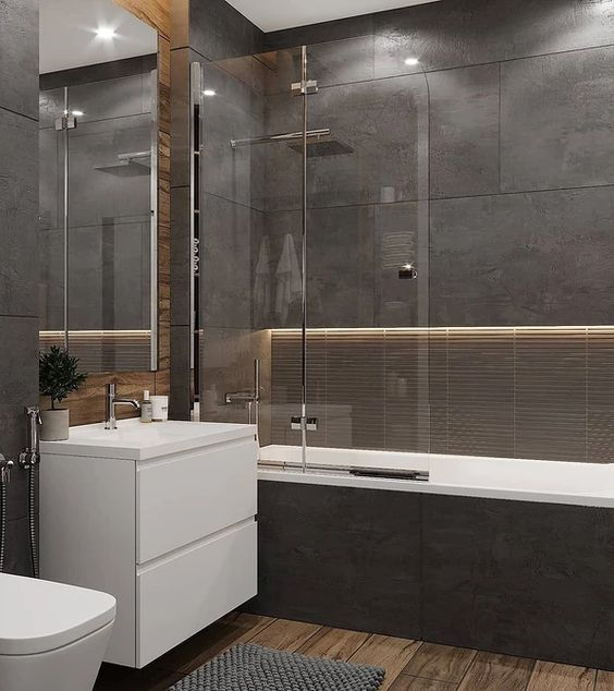 a moody contemporary bathroom clad with dark stone tiles, with built-in lights, a wooden floor, white appliances and neutral fixtures