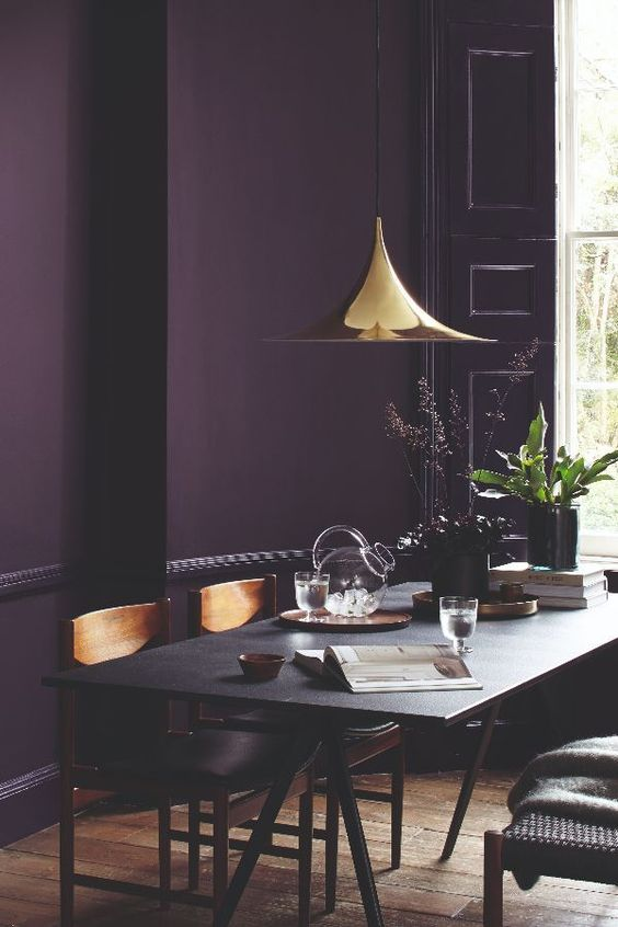 a moody dining room with a deep purple accent wall, a black trestle table and wooden chairs, a shiny gilded pendant lamp