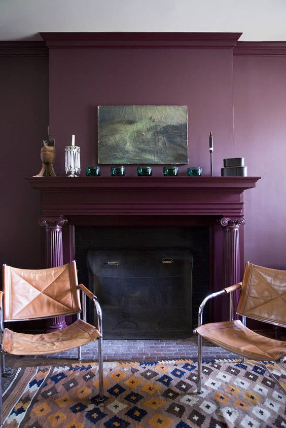 a moody living room with a deep purple accent wall, a fireplace done in the same color, leather chairs and some decor on the mantel