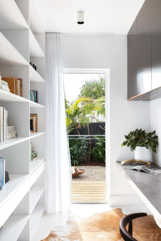 a narrow contemporary home office with an oversized white shelving unit, a floating desk and dark storage cabinets