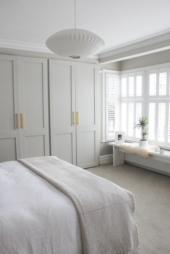a neutral Zen bedroom with a large closet with shaker style doors, a bench with a potted plant and some artworks and a pendant lamp