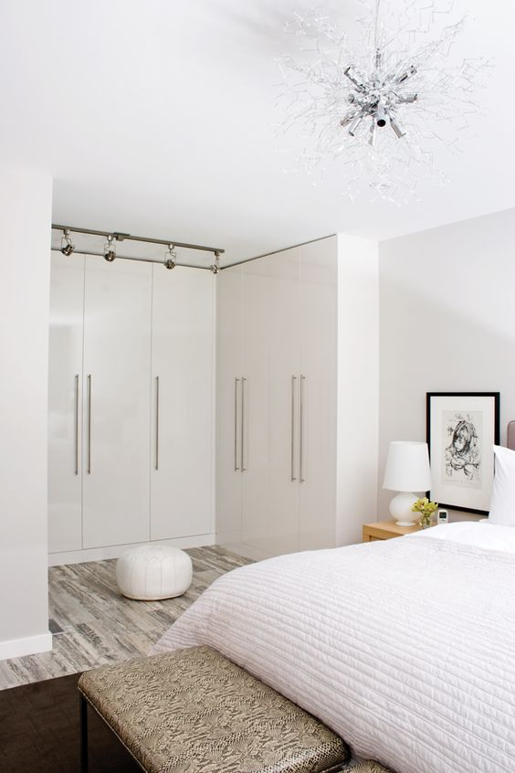 a neutral and chic bedroom with a gorgeous chandelier and a closet organized here, with sleek doors for a decluttered look