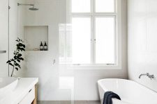 a neutral and lightweight bathroom with large scale tiles, an oval tub, a large vanity and dark touches for a fresh look