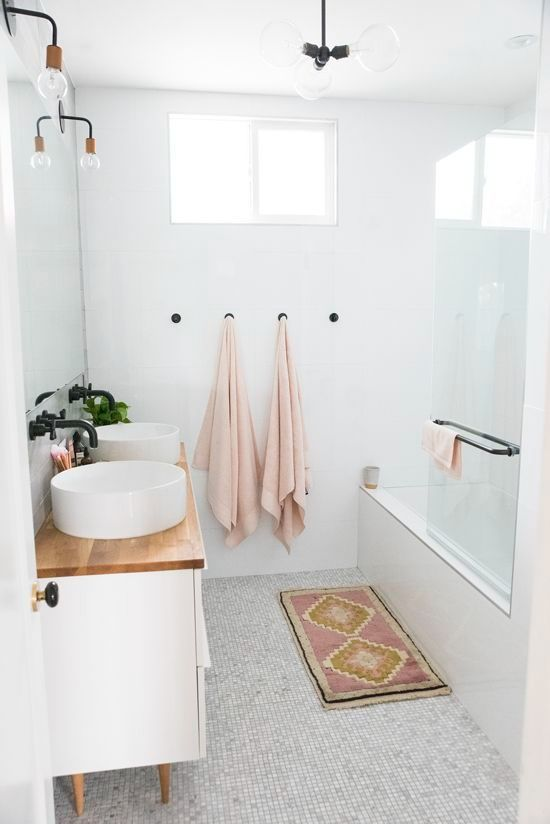 a neutral bathroom clad with different tiles, a white vanity with round sinks, pastel towels and black fixtures is a very chic space