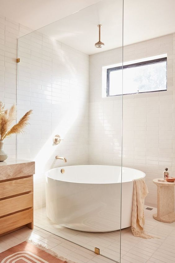 a neutral contemporary boho bathroom with white skinny tiles, a round tub, a wooden vanity and brass fixtures is a chic space