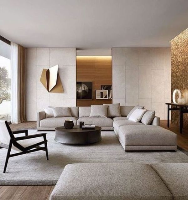 a neutral contemporary living room done in light greys, with a corner sofa, a daybed, a wooden chair, a round table, built-in lights