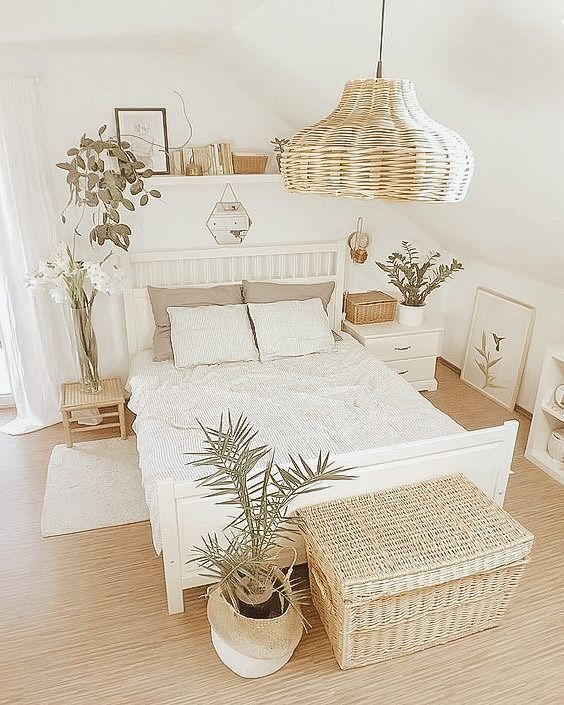 a neutral farmhouse bedroom with white and stained furniture, a woven pendant lamp and a woven chset, potted plants and a floating shelf