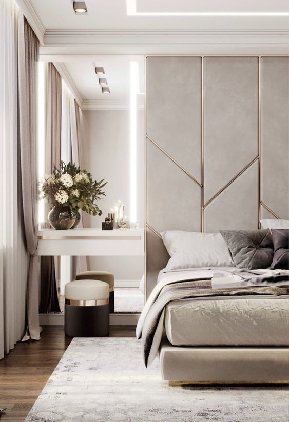 a neutral luxurious bedroom with a grey and metallic accent wall, a grey upholstered bed, a floating nightstand and a tall mirror