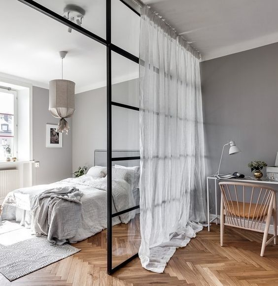 a pretty Scandinavian bedroom in shades of grey, with a glass space divider for a home office nook is a functional idea