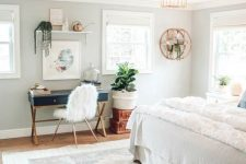 a pretty boho bedroom with a navy desk and a faux fur chair, a floating shelf and potted plants, neutral bedding and a printed rug