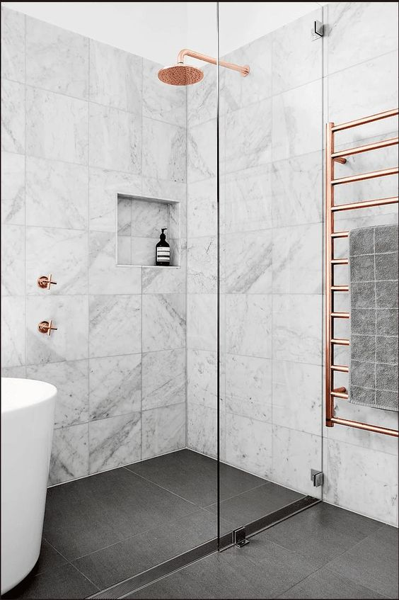 a pretty contemporary bathroom clad with white marble tiles, a soak tub, copper fixtures and a grey tiled floor is very chic