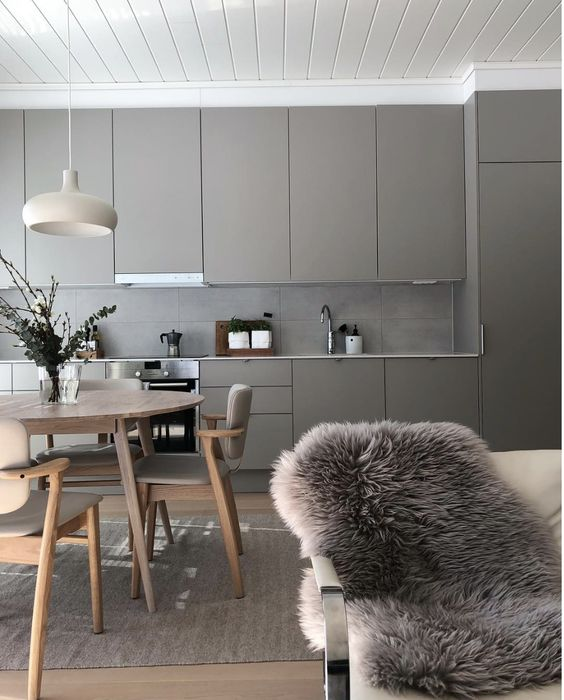 a pretty greige kitchen with sleek cabinets and a concrete tile backsplash, a neutral and cozy dining space here
