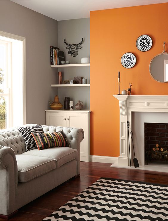 a pretty monochromatic mid-century modern living room done in grey, black and white and cheered up with a bold orange accent wall