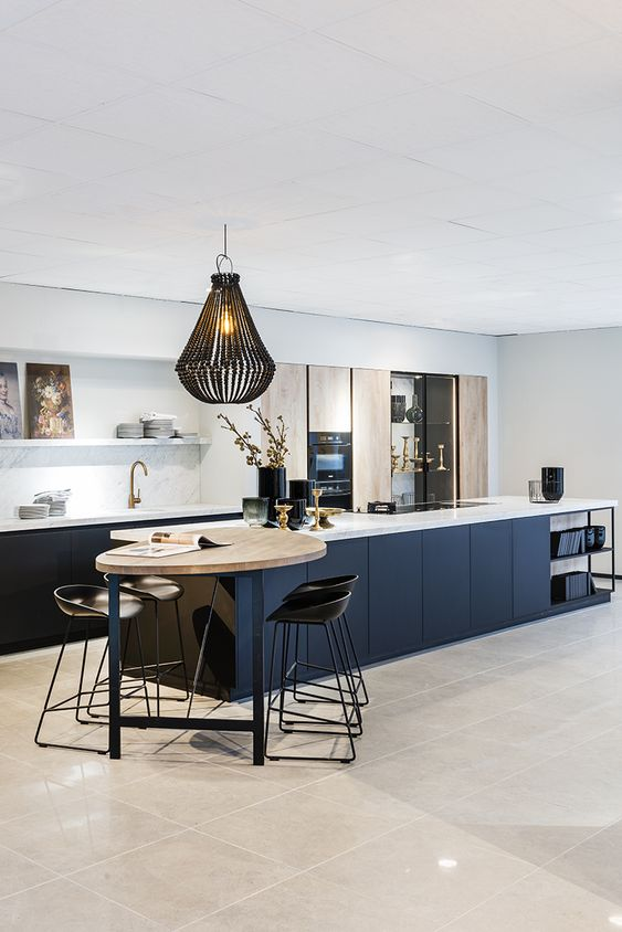 a refined contemporary kitchen with navy lower cabinets and a kitchen island, ligth stained doors, open shelves and a small meal zone