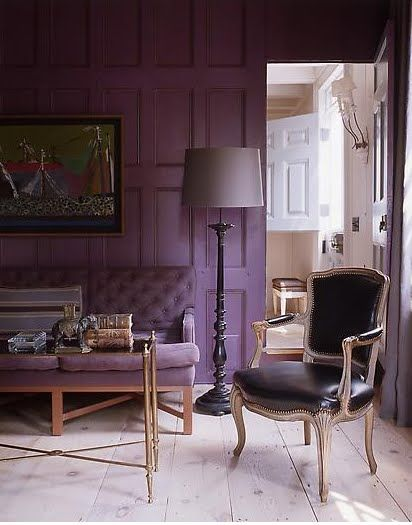 a refined living room with a purple accent wall and a matching sofa, a refined table with gold legs, a black leather chair and a grey floor lamp