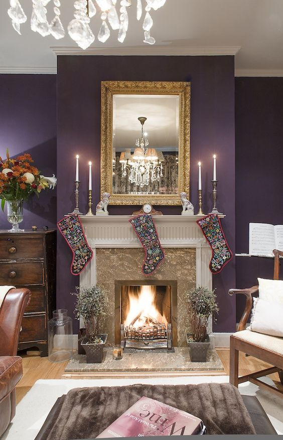 a refined living room with an aubergine accent wall, a fireplace, a mirror in a vintage frame, stockings and a crystal chandelier