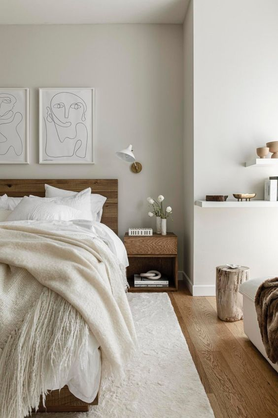 a refined minimalist bedroom with stained furniture, a floating shelf, tree stumps, sconces, a grid gallery wall and neutral textiles