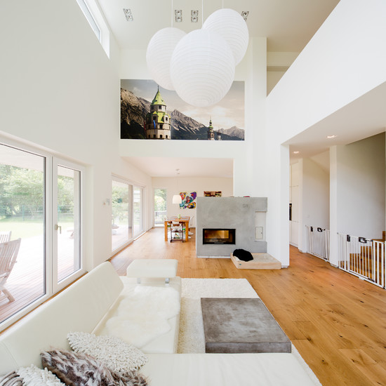 a relaxed contemporary living room with a creamy sectional and a rug, a grey mini table, a concrete fireplace, pendant lamps
