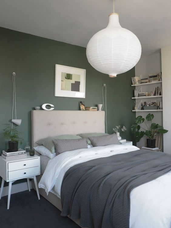 a relaxing modern bedroom with a green accent wall, open shelves, an upholstered bed with neutral bedding, white nightstands and a pendant lamp
