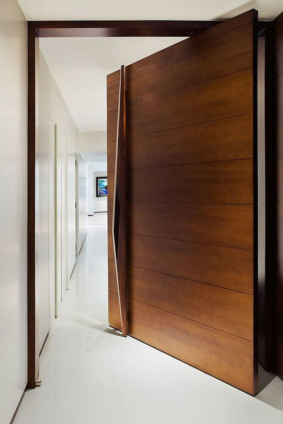 a rich-stained wood clad pivot door with a large and sculptural handle that adds a refined and chic touch to the space