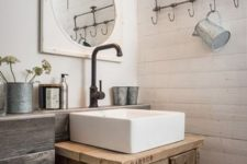 a rustic bathroom with white planked walls, reclaimed wood and a reclaimed wood vanity, dark metal fixtures and vintage touches