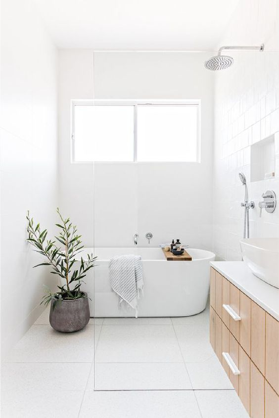 a serene bathroom in neutrals, with square large scale tiles, a wood floating vanity, a niche shelf and a potted plant