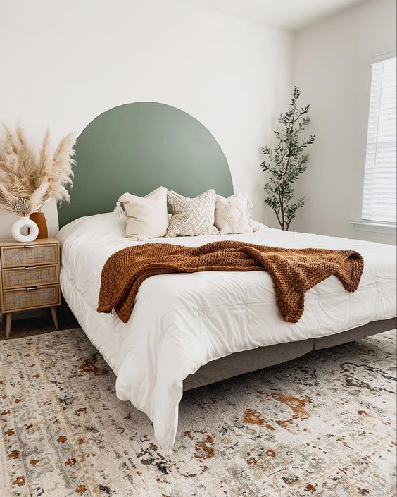 a serene bedroom with an upholstered bed, neutral bedding, cane nightstands, potted plants and a green headboard painted on the wall