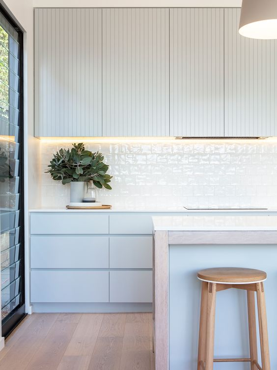 a serene contemporary kitchen with pale blue cabinets, planked and sleek ones, white glazed tiles and a matching blue kitchen island