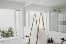 a serene white contemporary bathroom with an oval tub, a floating vanity, a long and large mirror and a ladder with towels