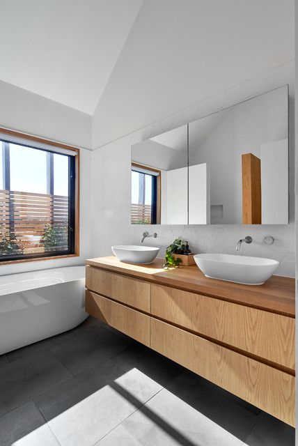a simple contemporary bathroom with a window, a tub, a concrete tile floor, a double light-stained vanity and a mirror storage unit