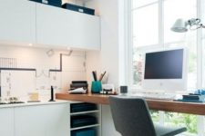 a simple contemporary home office in white, with a floor to ceiling window, sleek cabinets, a floating desk, built-in lights and with a cool view