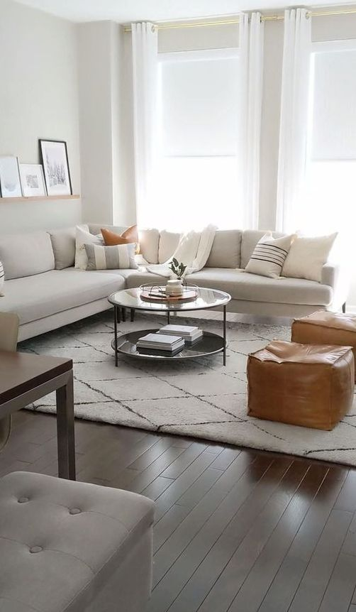 a simple contemporary living room with a sectional, amber leather poufs, a round coffee table, printed pillows and a ledge with artworks