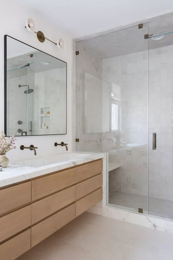 a sleek contemporary bathroom with a shower space clad with marble, a floating vanity with a marble countertop, a mirror and brass fixtures