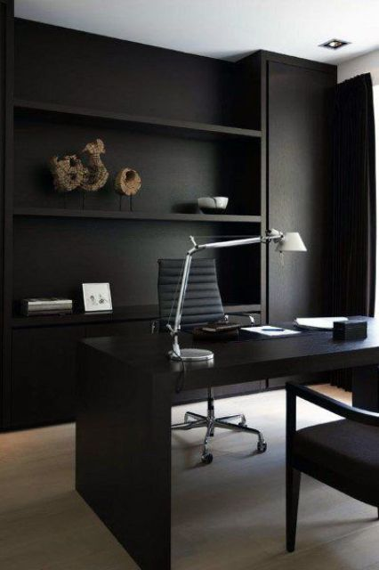 a sleek contemporary home office in black, with built-in storage units and shelves, a black desk and a grey chair