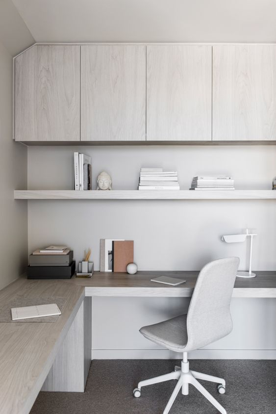a sleek contemporary home office in light greys and white, with sleek storage units, an open shelf and a large corner desk plus a grey chair