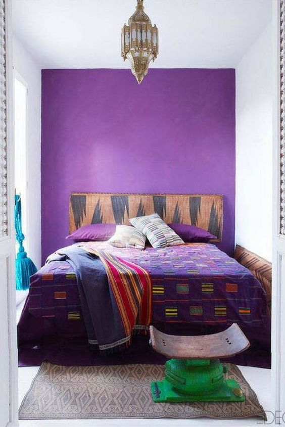 a small and colorful boho bedroom with a purple accent wall, a bed with bright bedding, a small stool and a Moroccan pendant lamp