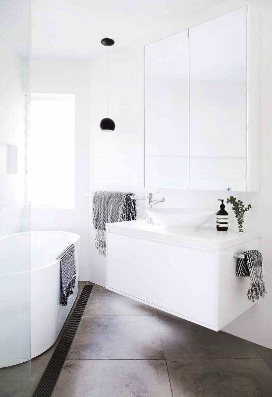 a small contemporary bathroom with a tub, a white floating vanity and a round sink, a large mirror and a shower