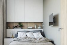 a small contemporary bedroom with sleek white storage units, an upholstered bed and a small nightstands, neutral bedding is chic