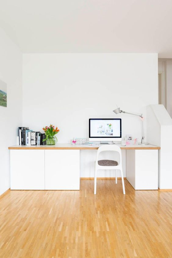 a small contemporary home office nook with a large desk with sleek storage units, a table lamp, some books and blooms is welcoming