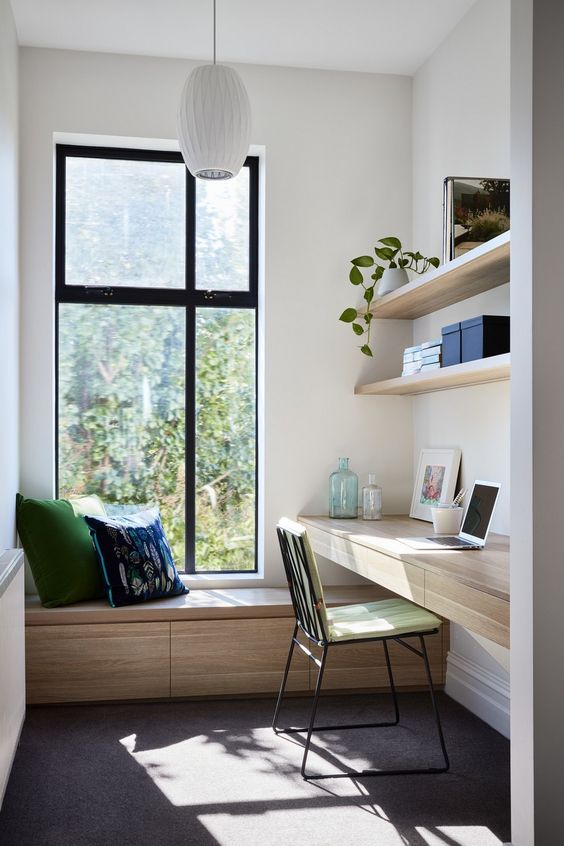 a small contemporary home office with a sleek storage daybed by the window, a floating desk, floating shelves and touches of green