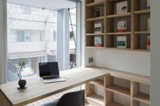 a small contemporary home office with open stained storage units, a built-in desk, a black chair and a glazed wall for a view
