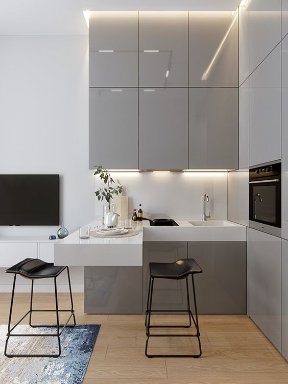 a small contemporary kitchen with sleek grey cabinets, a white floating countertop and a backsplash, some built-in appliances