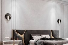 a sophisticated and luxurious contemporary bedroom with neutral paneled walls, a dark upholstered bed, various lamps and cracked touches with gold
