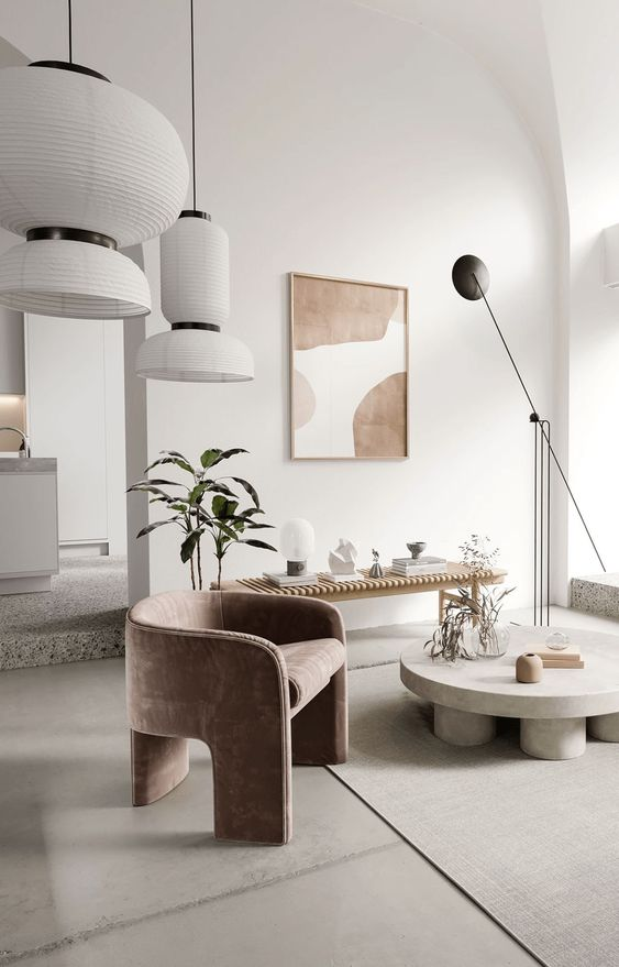 a sophisticated contemporary living room with a curved dusty pink chair, a round coffee table, a wooden bench, potted greenery, astatement artwork and lots of lamps