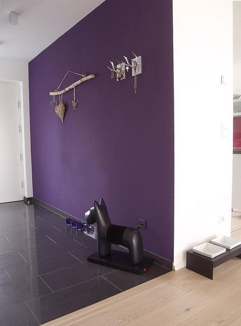 a statement entryway with a deep purple accent wall, candleholders right on the floor, a quirky floor lamp and some decor on the wall