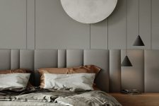 a striking contemporary bedroom in greys, with a grey accent wall, a wooden bed with an extended headboard and pendant lamp