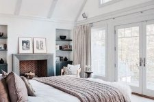 a stylish and welcoming attic bedroom with a fireplace clad with brick, a bed and dark stained nightstands, neutral textiles and a printed rug